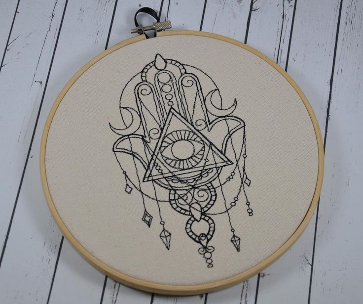 """Hamsa design, machine embroidered on natural canvas. It is framed in an 8"""" wooden hoop and has a ribbon to hang it on the wall. Long believed to contain magical properties ensuring good luck for the p"""