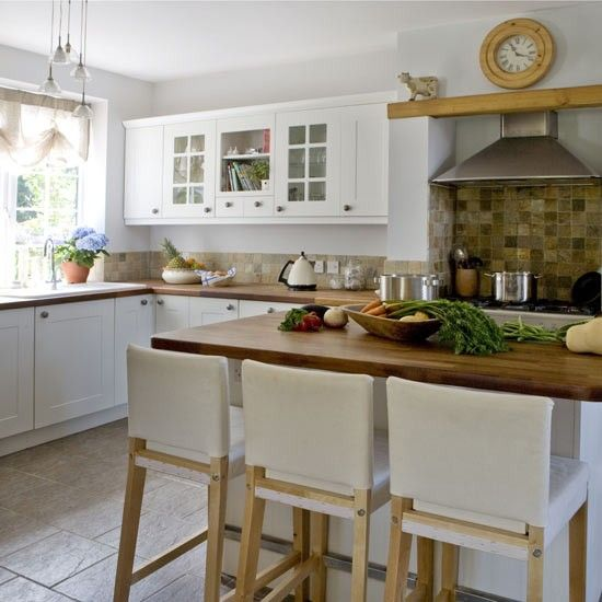 Simple white-painted kitchen units with wooden worktops create a cottage-style feel in this kitchen. Three matching bar stools are lined up next to the central island to create a welcoming breakfast bar. An earthy tile splashback makes a striking statement, while some of the Shaker-style wooden doors are replaced with glass so pretty items can be on display.  Kitchen units and worktop  Wickes  Stools  IKEA