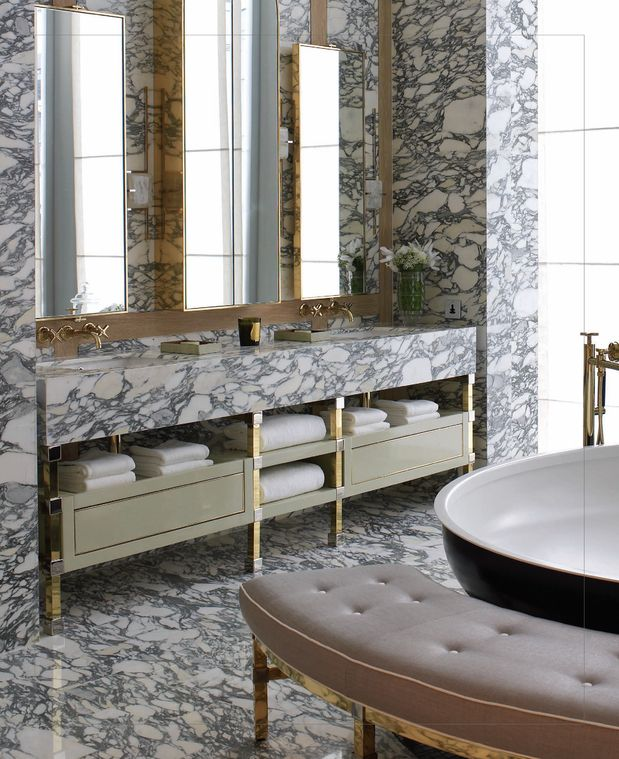 Heavily figured marble, gold accents, a triptych in mirrors above a beautiful double vanity, a black enameled freestanding bathtub, and a tufted, contoured bench to match?  This is what bathroom heaven looks like!