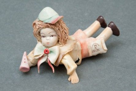 Pretty Baby at play statuette in Capodimonte porcelain finely decorated with trumpet, yellow apron, hat and hair spaghetti style. www.apoggi.com     Dimensions cm. 6x12