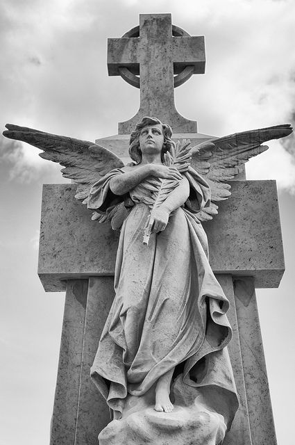 Statue of an Angel bearing an olive branch under a cross on a mausoleum by thaths, via Flickr