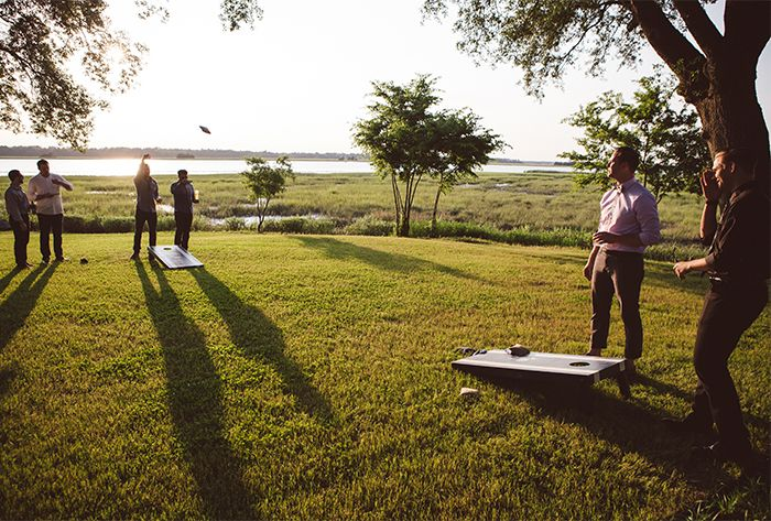 Lawn games like cornhole at The River House in Charleston, SC are a great way to celebrate with your team during a holiday or end-of-year party| Photo by Amelia and Dan