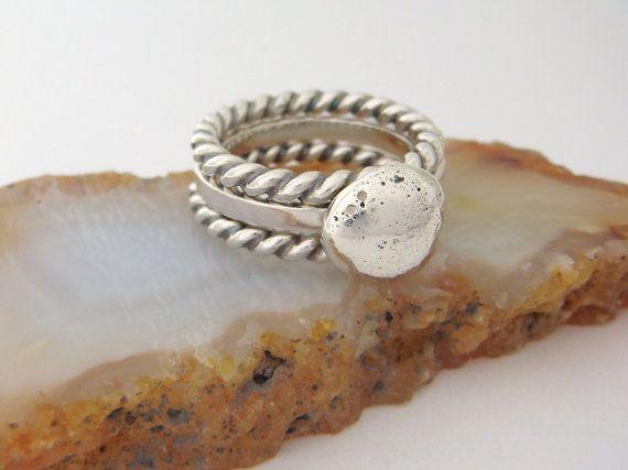 Deze reeks van stapelbare ringen van sterling zilver voegt een modern expressieve tintje aan uw hand! Gemaakt door mij, in mijn eigen winkel, geheel heb ik de nugget op de focal ring gemaakt door bits van sterling zilver smelten in een zware nugget. De nugget is gemonteerd op een handgemaakte, vierkante draad, sterling silver ring schacht. Ik heb de buiten stapelen ringen gemaakt van verdraaide sterling zilver draad. Ik heb de gedraaide draad ringen geven diepte en definitie aan de wendingen…