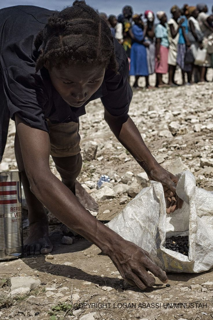 A woman picks up spilt beans at a food distribution in Gonaives, Haiti after a hurricane passed through the region causing mass floodings. Photo Logan Abassi UN/MINUSTAH