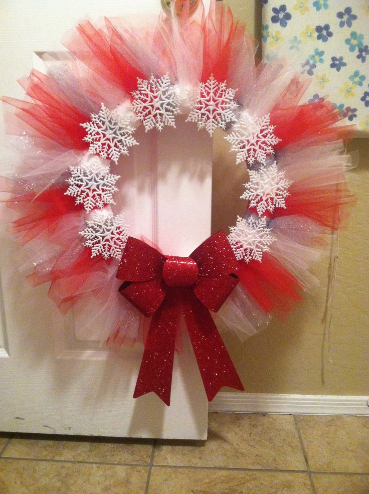 Christmas tulle wreath made with red white and silver tulle. Cut at 16 1/2 inches and double knotted around styrofoam ring. Cheap snowflake ornaments (hobby lobby) and an inexpensive bow (hobby lobby)