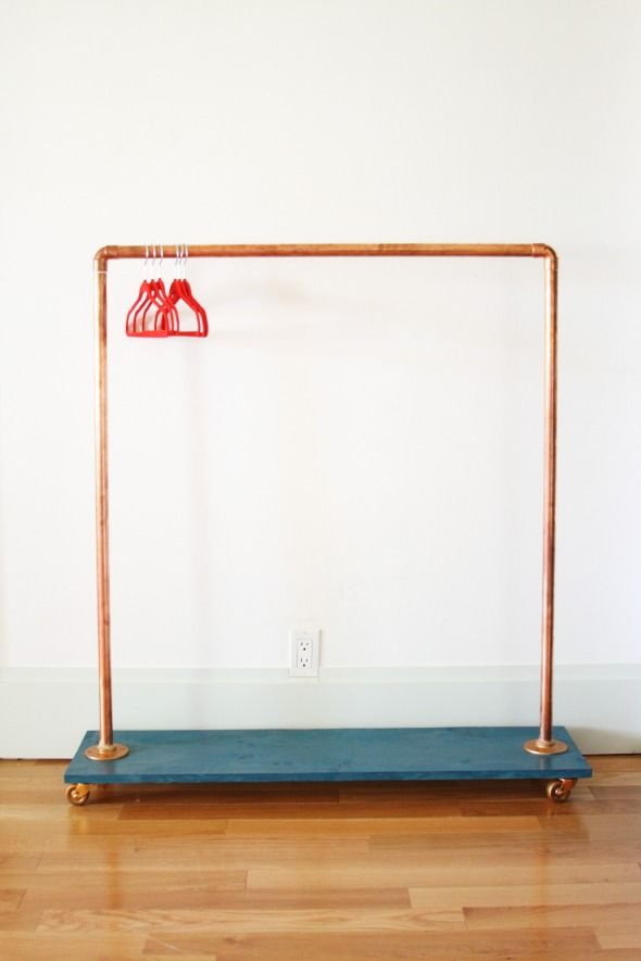 DIY clothing rack made from copper pipe, floor flanges, elbow connectors, casters and pine board.
