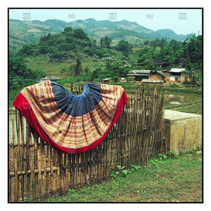 [photo by Francis Roux] Hand embroidered Hmong dress draped over a bamboo fence amidst the vast green landscape of Bac Ha in Northern Vietnam, Southeast Asia