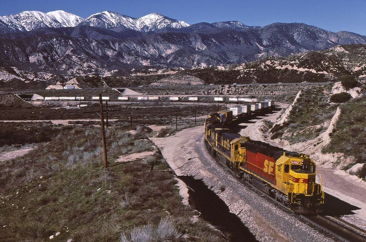 https://flic.kr/p/DiVRi1 | Kodachrome on Cajon | SD45u 5402 was one of the first units to get the ill-fated SPSF merger scheme in 1985. Here it leads an eastbound shooter over Cajon Pass near the old station site of Alray a year later. Santa Fe painted over 300 units in this scheme before the merger was denied. Railroaders being what they are with acronyms and initials, somebody quickly declared that SPSF stood for Shouldn't Paint So Fast.