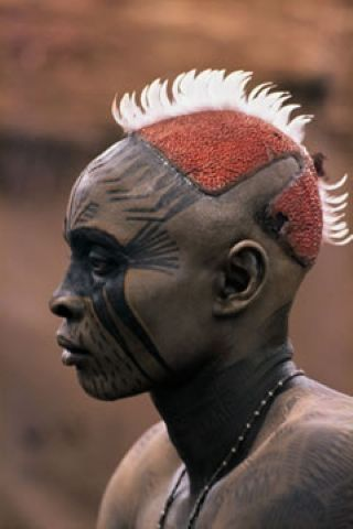 Sudan | A Nuba from Kau with his painted face mask.