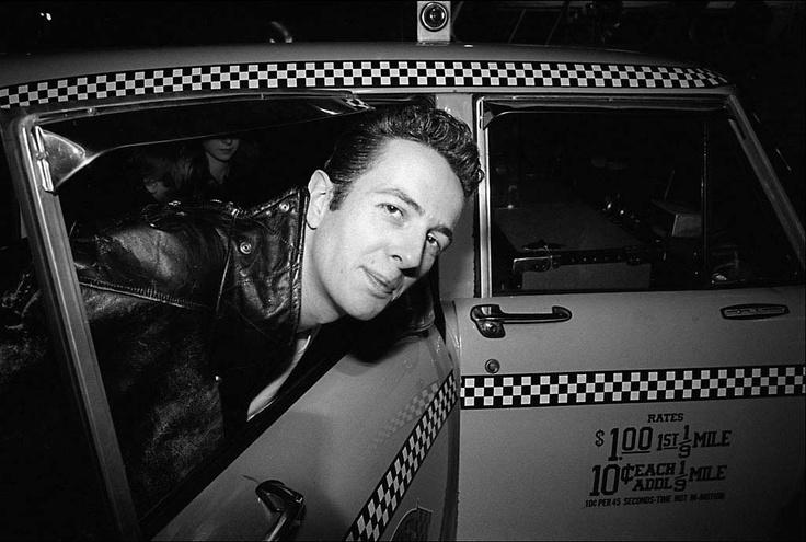 The Clash arrive at JFK - Mick Jones, Joe Strummer, Paul Simenon. Joe Strummer getting out of a taxi. ©2002 Allan Tannenbaum