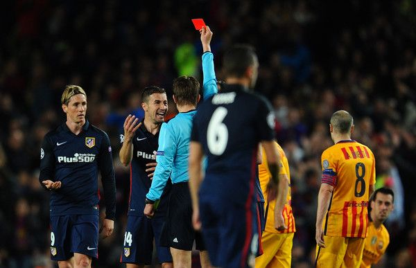 Fernando Torres of Atletico Madrid (L) is shown a red card by referee Felix Brych and is sent off during the UEFA Champions League quarter final first leg match between FC Barcelona and Club Atletico de Madrid at Camp Nou on April 5, 2016 in Barcelona