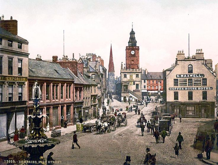 Horse and carriages line the high street in Dumfries, with pedestrians walking past an old Coffee House Hotel