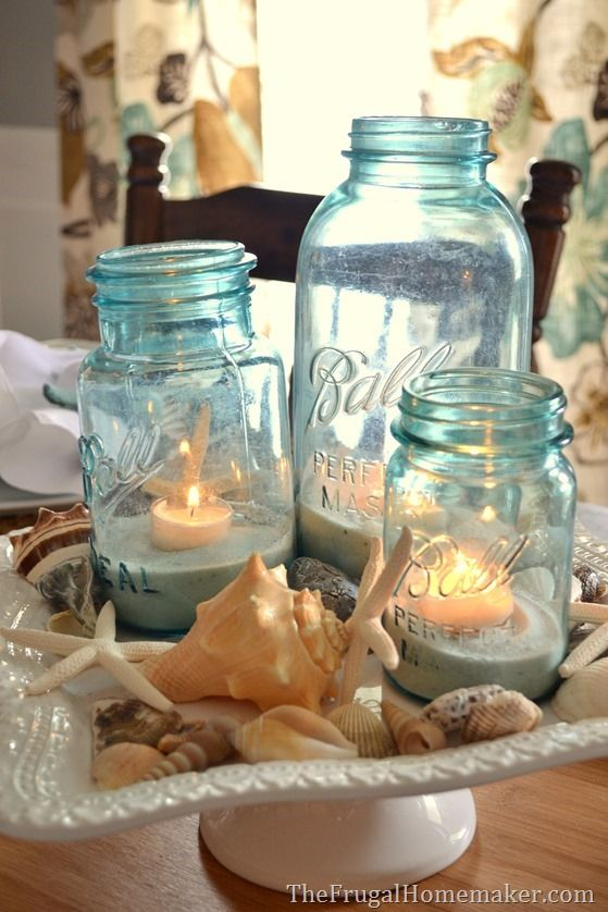 blue mason jars displayed on a cake stand with shells