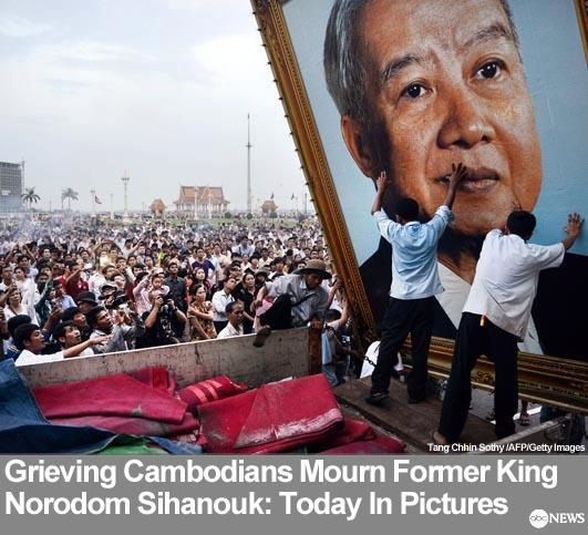 More of Today in Photos: http://abcn.ws/101612    Cambodian people watch as workers install a portrait of the late former king Norodom Sihanouk in front of the Royal Palace in Phnom Penh, Camobodia, Oct. 16, 2012. Grieving Cambodians wore black ribbons and flags flew at half-mast Oct. 16 as the nation mourned the death of revered ex-king Norodom Sihanouk and prepared for the return of his body from China.