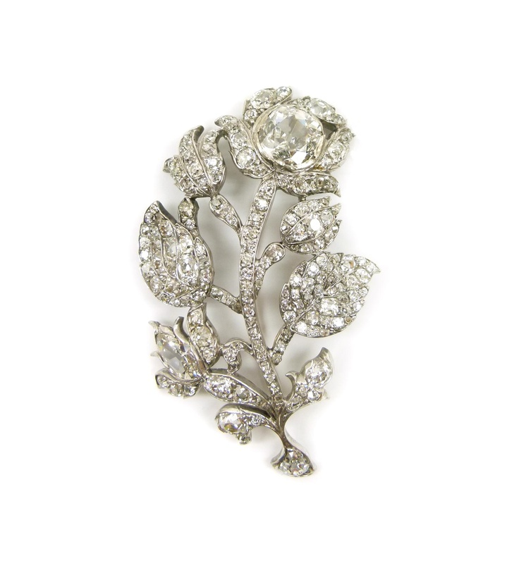 19th century diamond flower brooch, c.1800,  designed as a spray of bell shaped flowerheads, one in full bloom to the top set with a principal cushion cut stone, one lower down set with a pear shape, further buds and leaves, open set throughout with round and cushion cut stones, mounted in silver and gold
