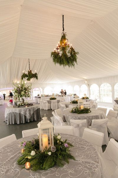 Winter wedding reception with a beautiful white draped tent and winter greenery decor {Arte De Vie}