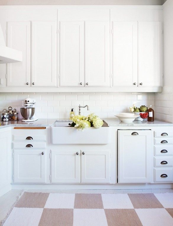 This kitchen stays in the white color family with sleek counters and subway-style tiles. The cream checkered rug breaks it up