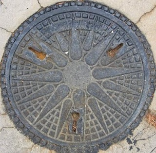 Star of Vergina pattern on manhole cover- Thessaloniki, Greece