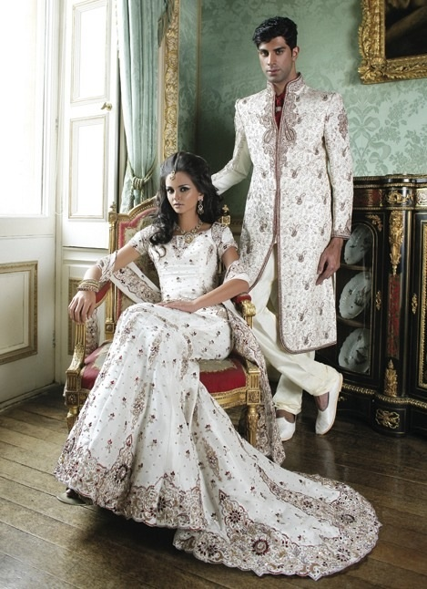 Bride and groom dressed in ivory/ white outfits