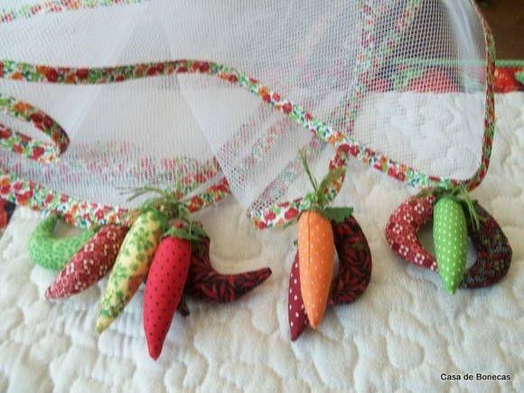Protetor de mesa em filó com debrum de viés de algodão e decorado com moranguinhos de tecido. Pode ser com outros motivos, como pimentas, foto ao lado.