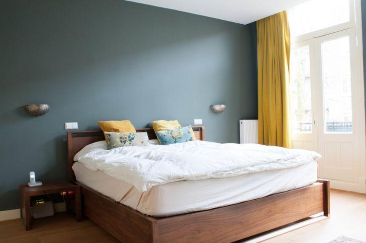 blaugraue Wandfarbe, Holzbett und gelbe Textilien