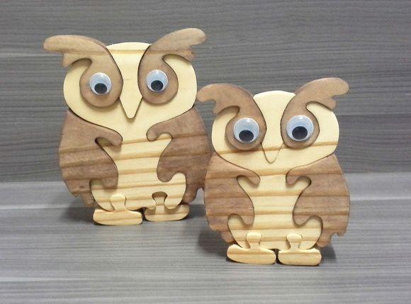 Dupla de corujas com olho móvel.. sendo a maior com 17 cm de altura e 14 de largura e a menor com 13 cm de altura e 10 cm de largura.  As duas corujas são compostas de peças desmontáveis, formam um quebra-cabeça em 3D.  Feito em madeira de reflorestamento.
