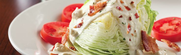 ... wedge with tomato slices, bacon crumbles and blue cheese dressing