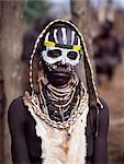 A Karo woman with her face painted in preparation for a dance in the village of Duss. A small Omotic tribe related to the Hamar, who live along the banks of the Omo River in southwestern Ethiopia, the Karo are renowned for their elaborate body painting using white chalk, crushed rock and other natural pigments. She is wearing a goatskin apron and carries a leather belt decorated with cowrie shells