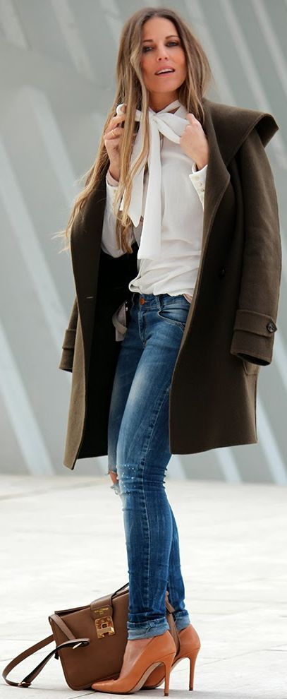 Pulled-together chic street style: crisp white bowtie blouse; denim; camel pumps; and long, tailored jacket.