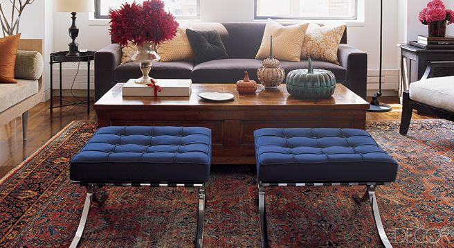 Vintage Miles van der Rohe Barcelona stools are upholstered in a #blue Donghia wool, and the cocktail table is antique.   - ELLE DECOR