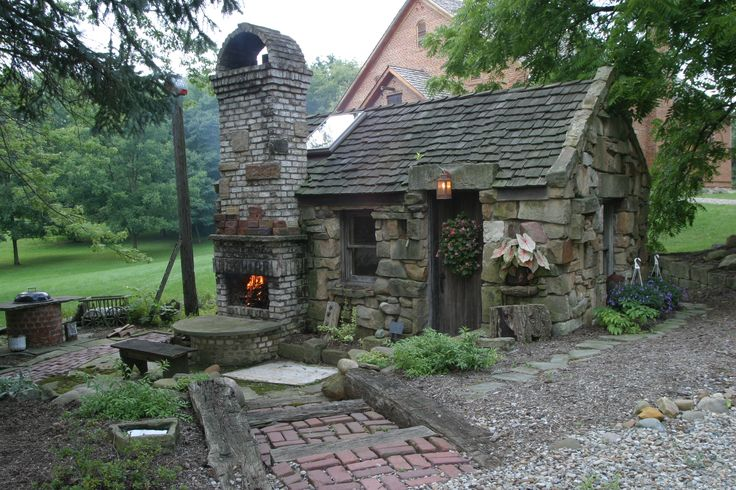 This is a good idea - an outdoor fireplace, garden shed and patio area. Love the stone.