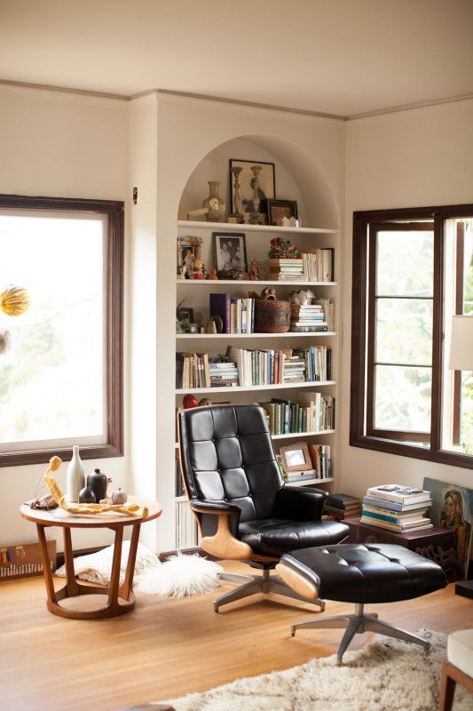 Perfect reading nook with built in curved bookcase and mid-century modern recliner