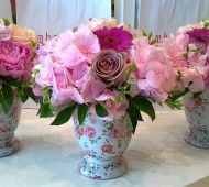 pink wedding table setting with flowers in vintage pots