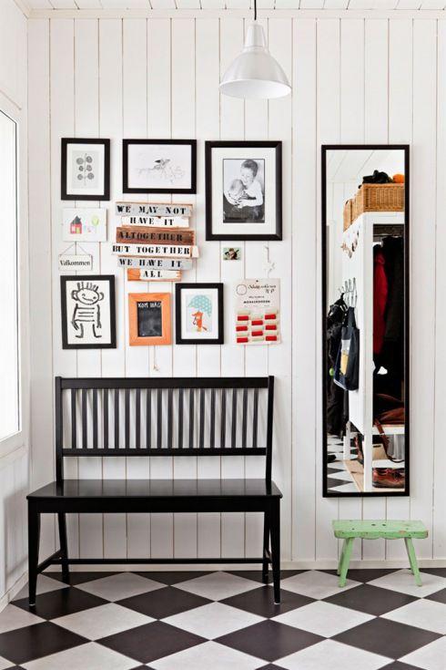 białe deski na scianie,czarna drewniana ławka,prostokatne czarne lustro i galeria grafik i lustracji na scianie w przedpokoju