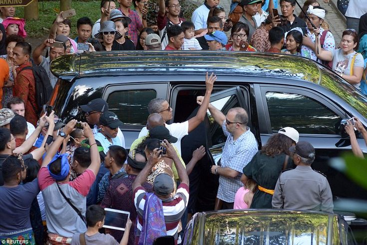 Crowds of onlookers surrounded the Obama's SUV to take photos and get a glimpse of the for...