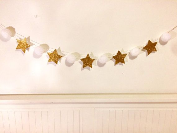 White and gold handmade pom pom bunting with 6 acrylic wool pom poms and 5 glittery gold card stars on white and gold twine. The pom poms are approximately 5cm in size and the garland is 110cm. This makes a perfect Christmas decoration to hang around the home or for parties and events and would look great above a fireplace. The garland ends with loops so it can easily be hung up. If you would like to customise the order please specify at checkout, e.g. cream pom poms and silver stars. Due…