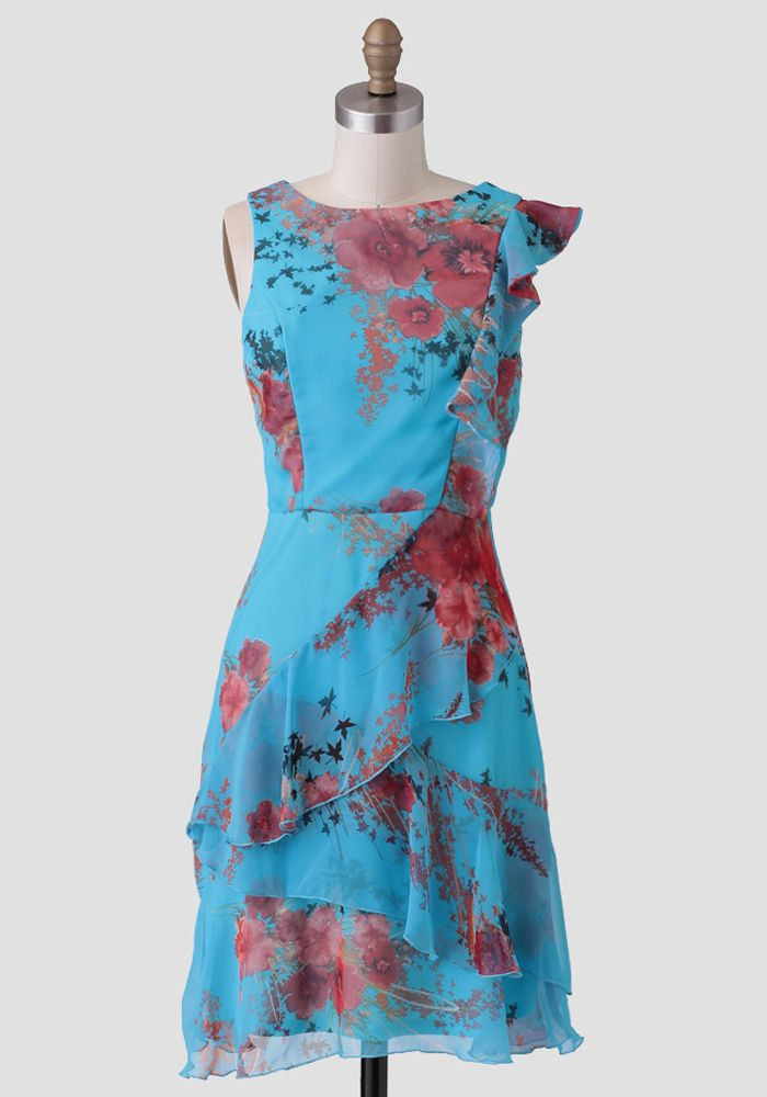 Rendered in a gorgeous light-blue shade, this intricate dress is adorned with a floral print in hues of red, black, and beige with ruffled accents across the front.