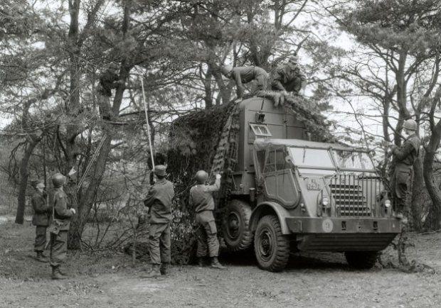Militairen van de Verbindingsdienst tijdens het in stelling brengen van een DAF YA-328, die in zijn opbouw een groot-vermogen radiotelex van het type AN/GRC 26A herbergt.