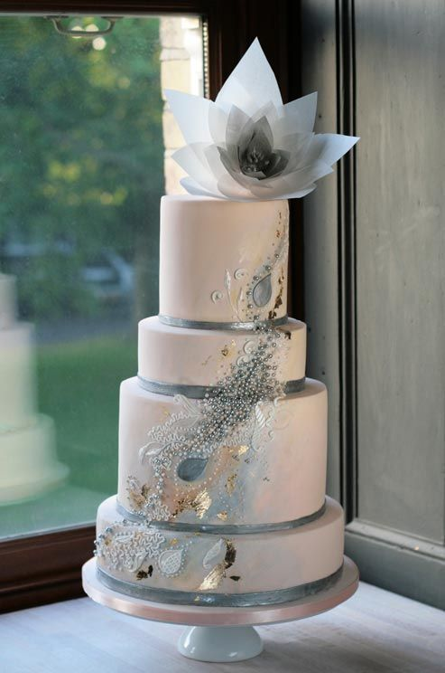 A mix of pearls, silver and gold gives a sleek beige cake artistic flare.