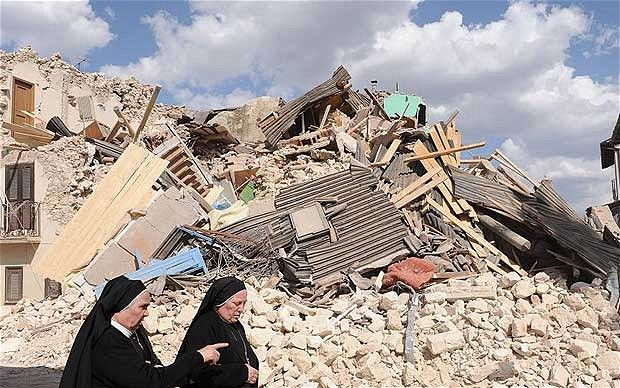 earthquake | Nuns walk past the ruins of a building after the earthquake on April 6 ...