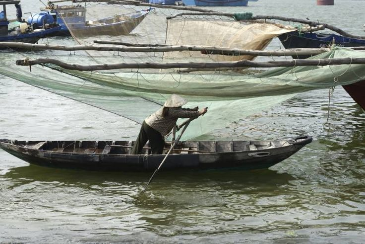 """Vietnamese woman paddling alongside Large Fishing Nets At The Fishing Village in Da Nang, South Vietnam"" #art"