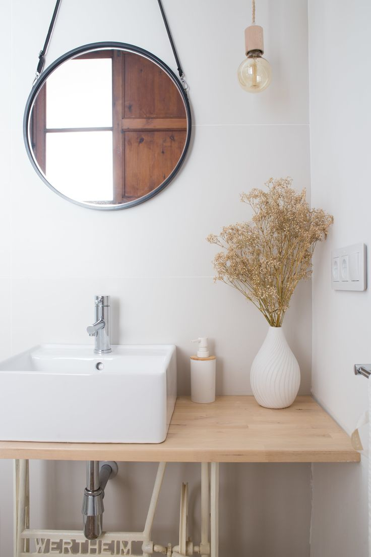 The bathroom features a Corian sink and Kenay Home mirror. An old sewing machine table was transformed into a modern bathroom washbasin.