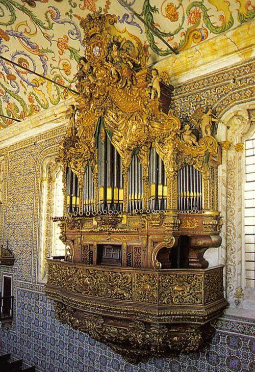 .ÓRGÃO DA CAPELA DA UNIVERSIDADE DE COIMBRA - O órgão, em estilo barroco, foi construído em 1733 por Frei Manuel Gomes; esse instrumento permanece funcional. Os azulejos da nave e capela-mor, do tipo de tapete, foram fabricados em Lisboa e datam do século XVII, assim como a pintura do teto, da autoria de Francisco F. de Araújo; o altar é do séc. XVIII. A imagem de Santa Catarina no nicho à direita do arco cruzeiro é do escultor Frei Cipriano da Cruz.