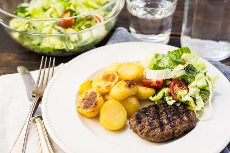 Recept voor gegrilde hamburger voor 4 personen. Met zout, boter, olijfolie, peper, hamburger, ijsbergsla, cherrytomaat, ui, munt, basilicum en aardappelen kruimig