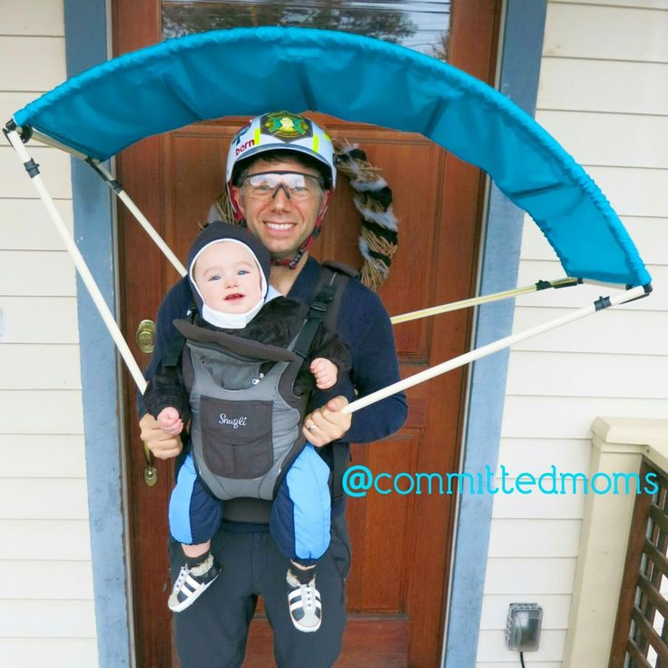 Baby carrier Halloween costume: tandem skydivers! Hats/bike helmets, snow pants, and a PVC-pipe parachute attached to the baby carrier with Velcro.