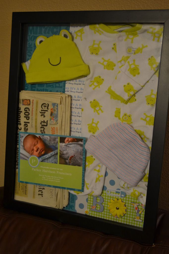 Newborn shadow box, outfit home, first hat, hospital bracelets, birth announcement, newspaper, footprints, bassinet card, coral ribbon from baby shower/ first nursery, date and weight, pictures.