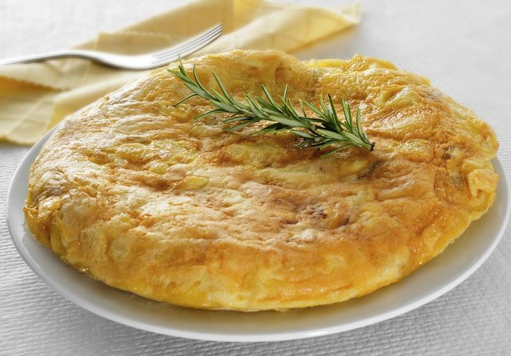 closeup of a plate with a typical tortilla de patatas, spanish omelet, on a set table