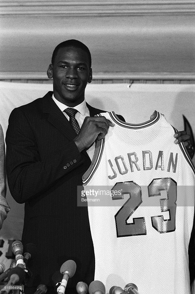 Former North Carolina star, College Player of the Year and star of the US Olympic gold medal winning basketball team, Michael Jordan holds up his Chicago Bulls jersey 9/12 at a news conference. Bulls General Manager Rod Thorn announced they have signed Jordan, their first round draft pick, to a multi-million dollar contract which is expected to make him the third highest paid in NBA history.