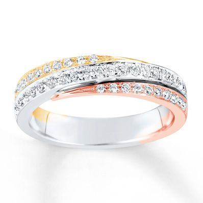 A wave of round diamonds set in 14K white gold is met above and below by swirls of 14K rose and yellow gold enlivened with additional diamonds in this contemporary anniversary band for her. The ring has a total diamond weight of 1/3 carat. Diamond Total Carat Weight may range from .29 - .36 carats.