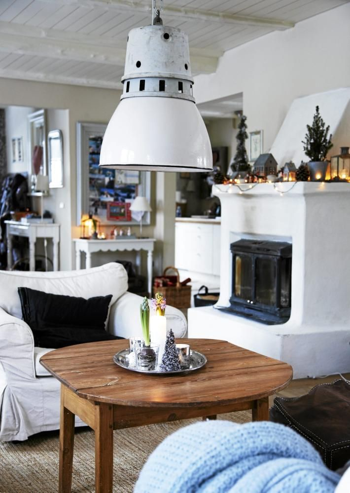 En stilig lampe i hvitt henger ned over salongbordet. Peishyllen er dekorert med levende lys og annen julepynt.